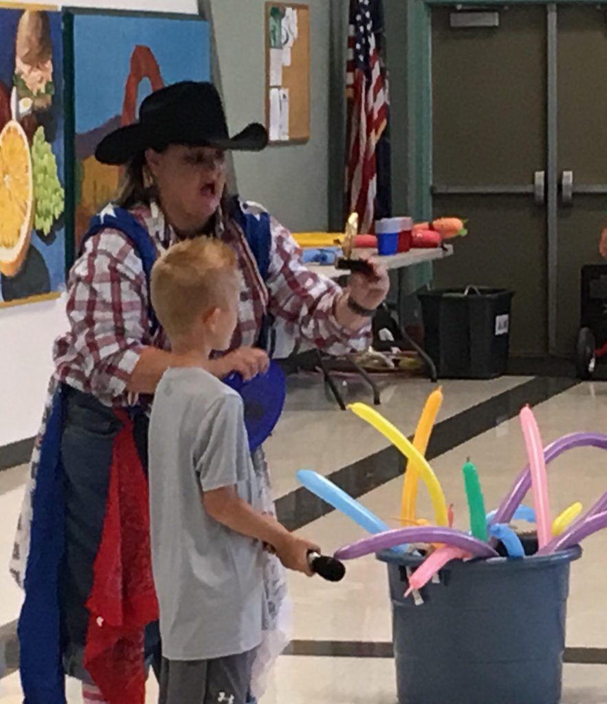 Mrs. Lyman helps student at Rodeo Assembly