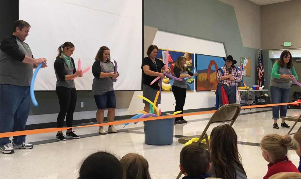 Teachers make balloon animals at rodeo assembly
